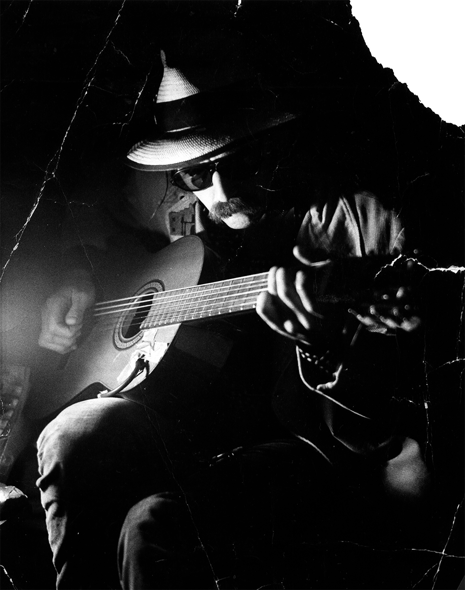 Black & white photo of Blaze in sunglasses at night, playing guitar