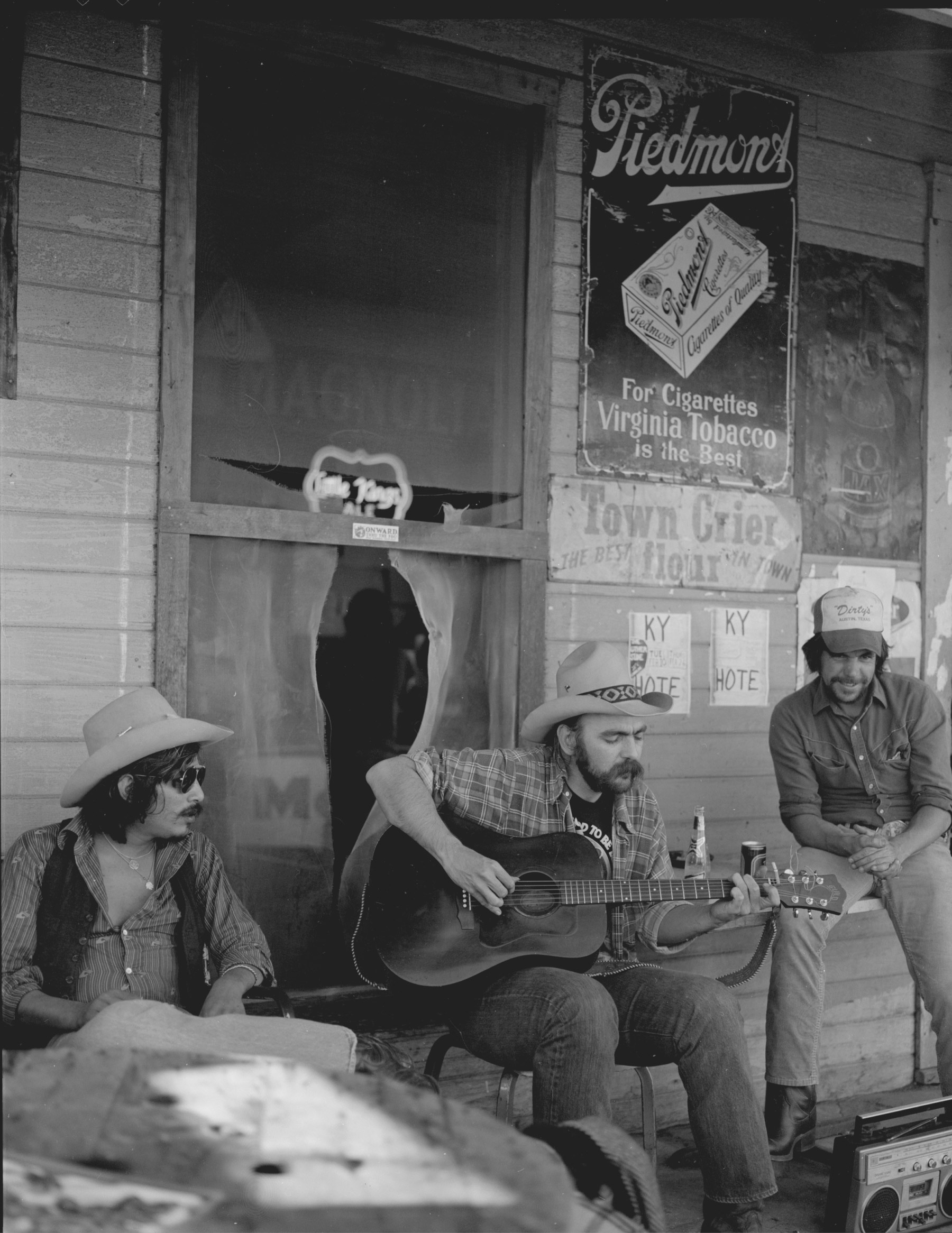 Blaze sitting on porch of a saloon, playing guitar for people