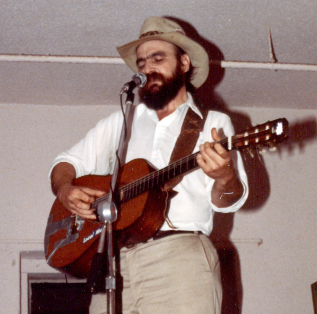 Blaze with beard, singing into microphone and playing guitar